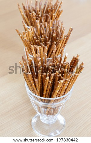Three Tall Glasses Filled with Pretzel Sticks on wooden surface. - stock photo