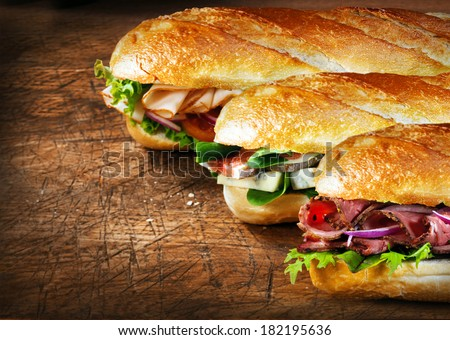 Three tasty baguettes with savory fillings lined up on a rustic wooden countertop with roast beef and rocket, figs and cheese, and chicken and salad fillings - stock photo