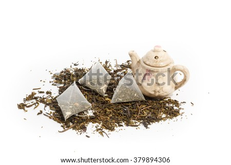 three tea bags, loose tea and teapot on white background  - stock photo