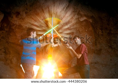 Three teen boys join light swords to create a star flare in a composited image. - stock photo