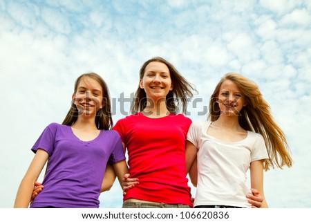 Three teen cheerful girls against blue sky - stock photo
