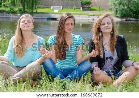 Three teen girls sitting in yoga position and meditating - stock photo