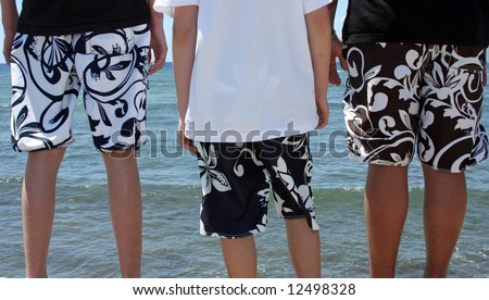 Three teenage boys in swim suits ready to jump into the water. - stock photo