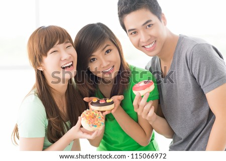 Three teenage friends offering little cakes
