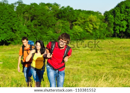 Three teenage friends with backpacks hiking - stock photo