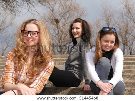 Three teenage girl sits on the stone stairs sunny day - stock photo