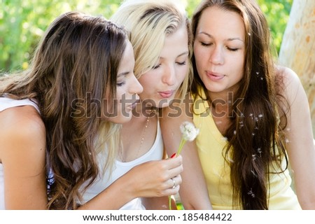 Three teenage girls blow away dandelion on summer day outdoors background portrait - stock photo