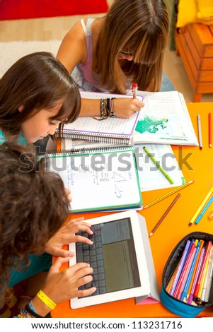 Three teenage girls busy with homework at desk.