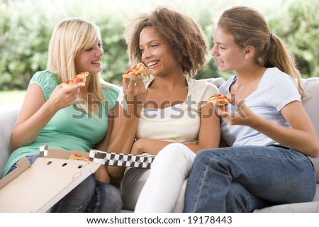 Three Teenage Girls Eating Pizza - stock photo