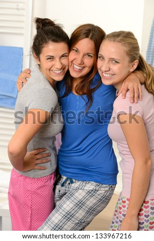 Three teenage girls friends laughing in pajamas together - stock photo