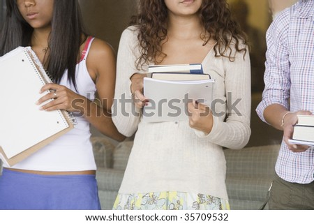 Three teenage girls ready for class and holding books - stock photo