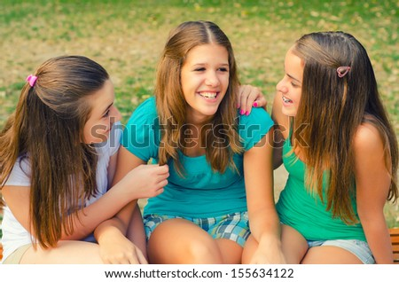 Three teenage girls talking and having fun in the park.