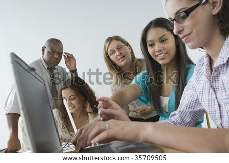 Three teenage girls working on a laptop with their teachers looking at them - stock photo