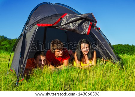 Three teenage hikers lying in the tent - stock photo