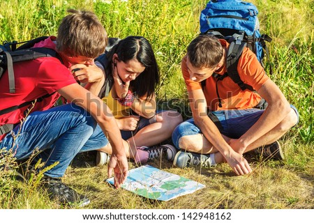 Three teenage hikers watching the map - stock photo