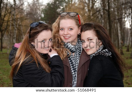 Three teenage smiling girlfriends in the spring park - stock photo