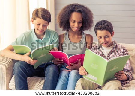 Three teenagers are reading and smiling while sitting on the couch at home. Attractive afro american girl is sitting between boys - stock photo