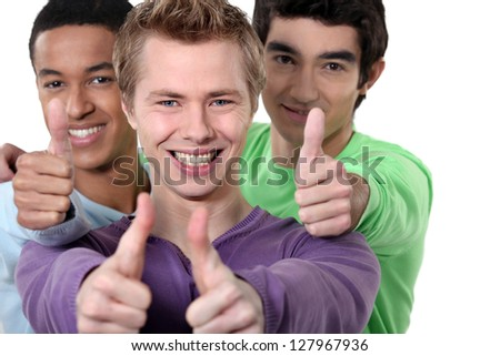 Three teenagers giving the thumbs-up - stock photo