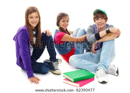 Three teenagers in casual clothes sitting in isolation - stock photo