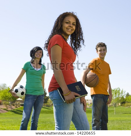 Three teens with a bible and sports equipment in a park - stock photo
