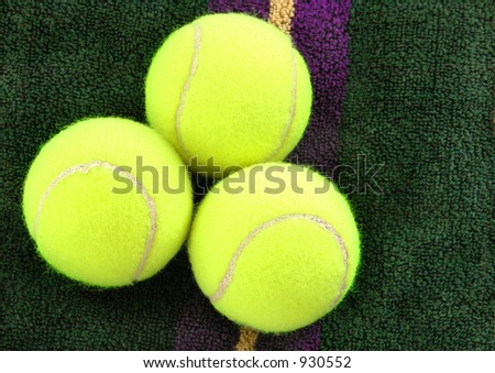 Three tennis balls on a purple and gold towel - stock photo