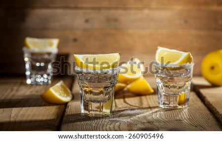 Three tequila shots with lemon and salt on wooden background.