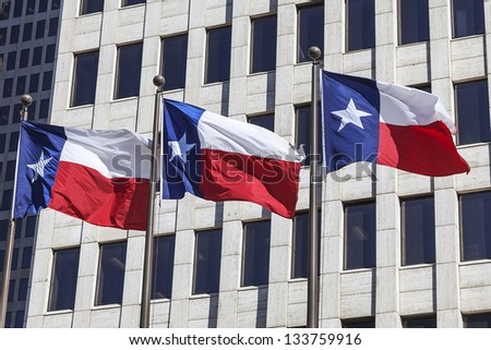 Three Texas flags are waving in front of the office Building. - stock photo