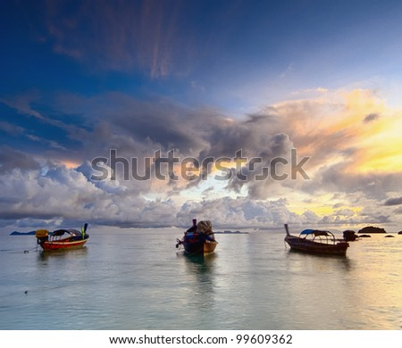 Three Thai longtail boat in the sea on sunrise