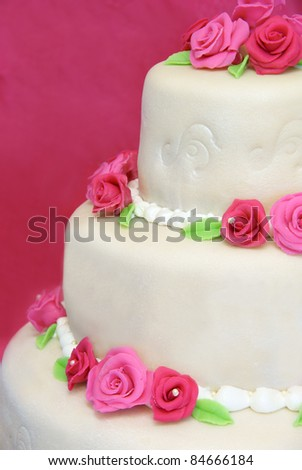 Three tier wedding cake decorated with pink marzipan roses - stock photo