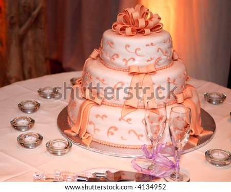 Three tiered wedding cake and champagne glasses on a table - stock photo