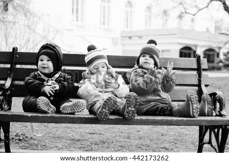 three toddlers are sitting on the bench