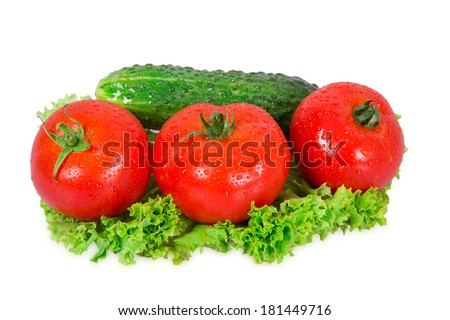 Three tomatoes and cucumber lie on lettuce leaf on a white background - stock photo