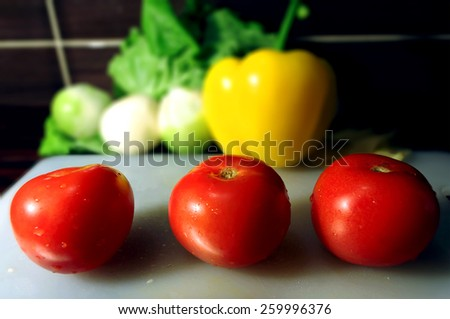 Three tomatoes on a background of other vegetables - stock photo