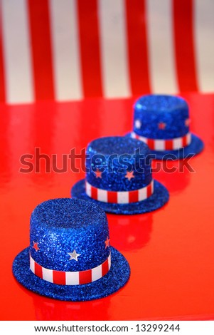 Three top hats with fourth of July theme on a red background. - stock photo