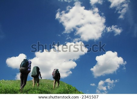 Three tourist going up along grassland - stock photo