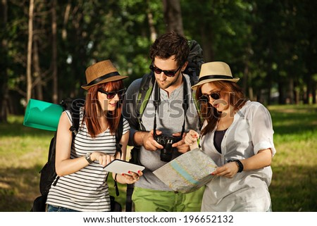 Three Tourists In Nature Browsing Map Using Digital Tablet - stock photo