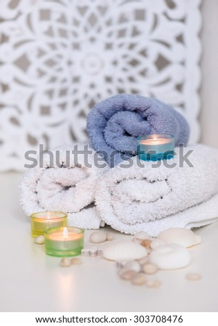 Three towels with candles and decorations on a white background - stock photo