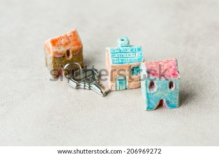 Three toy ceramic houses symbolizing real estate with a metal keys  beside - stock photo