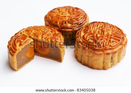 Three traditional Mooncake with one cut up to show egg yolk - stock photo