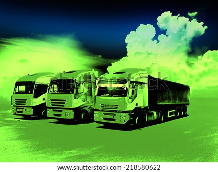Three trucks with trailers parked on field in green neon light - stock photo