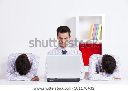 Three twin businessman, one is working with the laptop the other two are sleeping - stock photo
