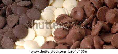 Three types of chocolate chips, dark, white and semi-sweet - stock photo