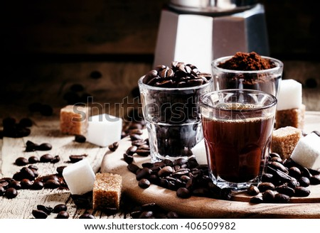 Three types of coffee: Grinded Arabica coffee beans, freshly brewed espresso, steel geyser coffee maker, vintage wooden background, selective focus - stock photo