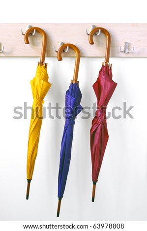 Three umbrellas hanging against the wall - stock photo