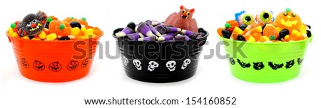 Three unique Halloween bowls filled with assorted candy - stock photo