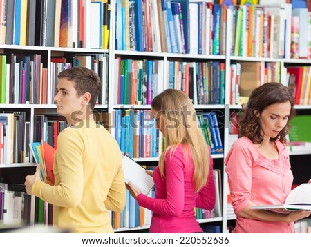 Three univresity students selecting books from shelves in a library. - stock photo