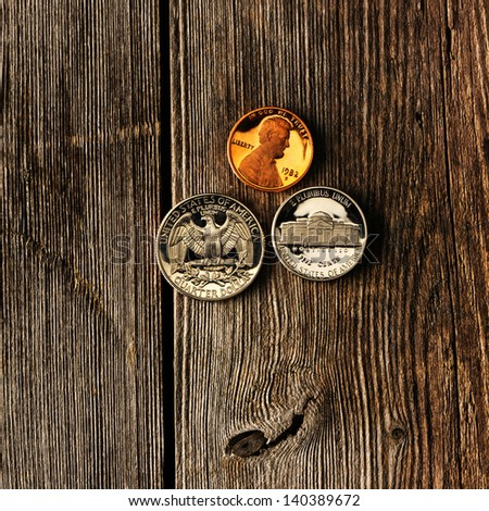 Three US cent coins over wooden background - stock photo