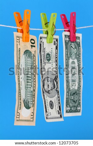 Three US dollar bills hanging on a washing line - stock photo