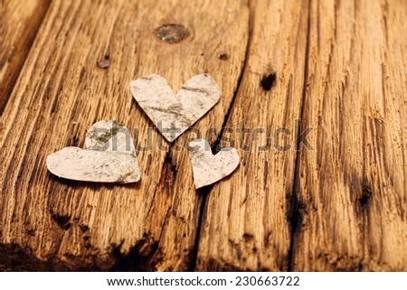 Three Valentine's hearts cut from birch bark are placed on very old wooden board with visible grooves - stock photo