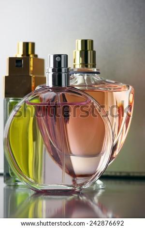 Three various bottles of woman perfume on gray background. - stock photo